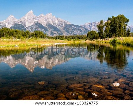The Teton Mountain Range is reflected in the shallow and still waters of a braid of the Snake River in Grand Teton National park, Wyoming, USA - stock photo