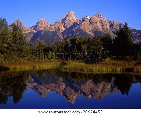 The Teton Range reflecting in the Snake River, at Schwabachers Landing, in Grand Teton National Park, Wyoming. - stock photo