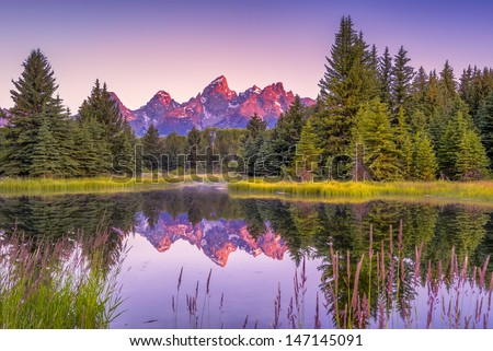 The Teton range's reflection upon the Snake River.  Photographed at dawn at Schwabacher's Landing in Grand Teton National Park, WY - stock photo