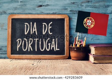 the text Dia de Portugal, Day of Portugal written in Portuguese in a chalkboard, and a flag of Portugal, on a rustic wooden table - stock photo
