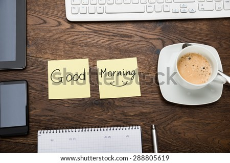 The Text Good Morning On Adhesive Note With Cup Of Coffee At Wooden Desk - stock photo