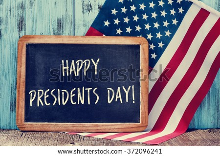 the text happy presidents day written in a chalkboard and a flag of the United States, on a rustic wooden background - stock photo