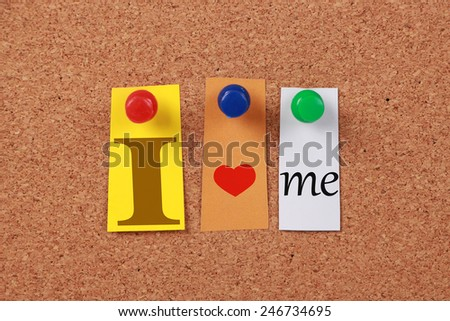 The text 'I love me' in cut out magazine letters pinned to a cork board. - stock photo