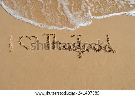 "The text ""I love thaifood"" written in the sand at the beach."