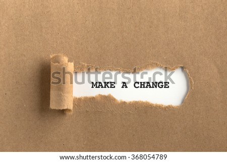 The text MAKE A CHANGE behind torn brown paper - stock photo