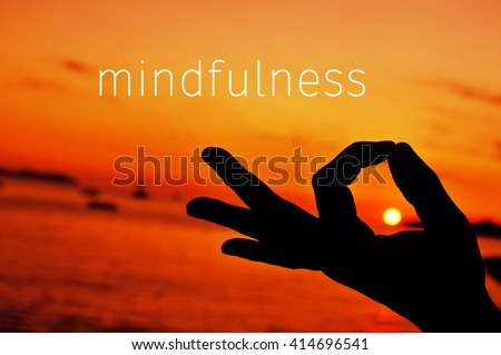 the text mindfulness and a closeup of a young man meditating with his hand in gyan mudra at sunset - stock photo