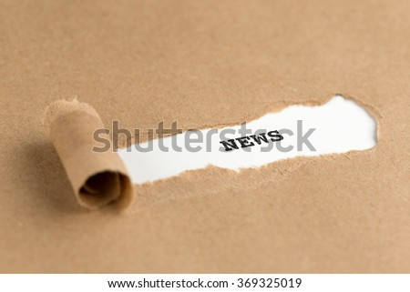 The text NEWS appearing behind torn brown paper - stock photo