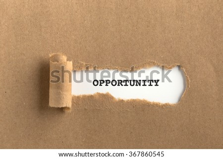 The text OPPORTUNITY behind torn brown paper - stock photo