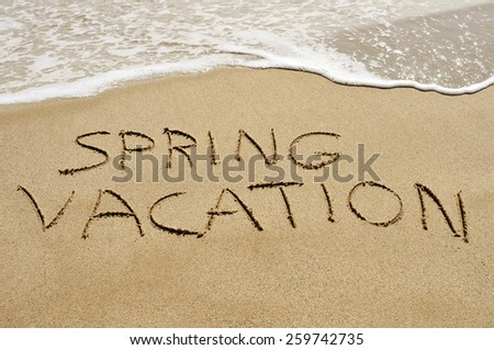 the text spring vacation written in the sand of a beach - stock photo