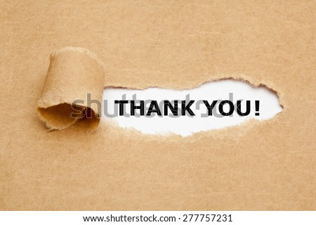 The text Thank You appearing behind torn brown paper. - stock photo