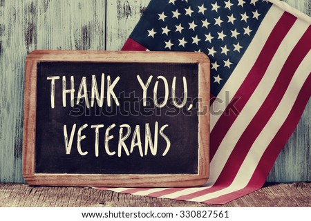 the text thank you veterans written in a chalkboard and a flag of the United States, on a rustic wooden background - stock photo