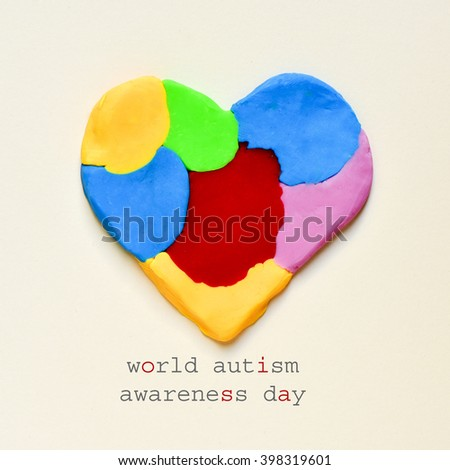 the text world autism awareness day and a heart made from modelling clay of different colors on an off-white background - stock photo