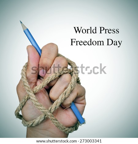 the text world press freedom day and the hand of a man, completely tied with rope, holding a pencil, depicting the idea of oppression or repression - stock photo