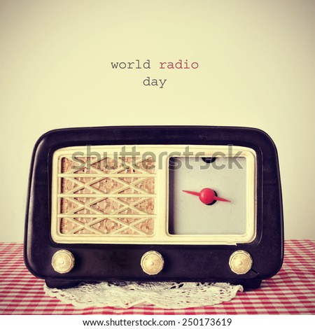 the text world radio day and an antique radio receptor on a table covered with a red and white checkered tablecloth, with a retro effect - stock photo