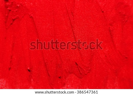 The texture of brush strokes of red lipstick. Background with dabs of red paint. - stock photo