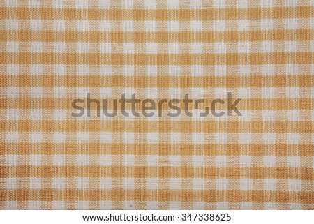 The texture of checkered fabric as a background. Checked fabric tablecloth. Fabric in a small square. Texture plaid fabric. Texture background of kitchen towels