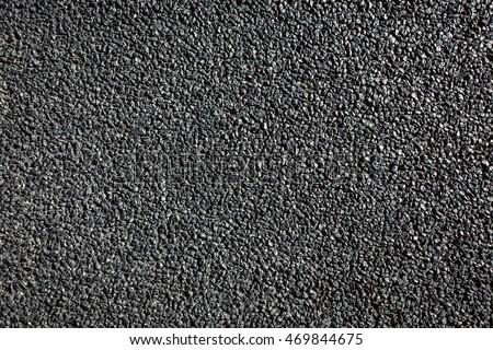 The texture of fresh asphalt lined up close. Pavement.