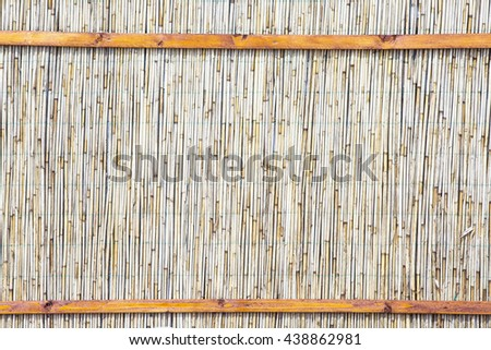 The texture of the dry reeds. Yellow reeds. A fence made of reeds. The roof is covered with reeds. Twigs. Sticks. Background. Tree. Dry grass. Cane. - stock photo
