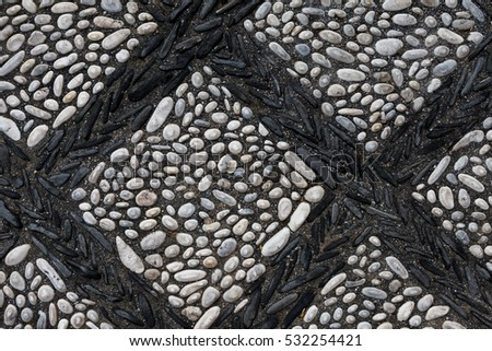 The texture of the old pavement of randomly laid cobblestones with with an ornament in the form of a lattice of the black stones in the monastery courtyard in Spain. View above