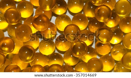 The texture of the round translucent gold balls on white background. Fish ROE, fish oil. Closeup - stock photo