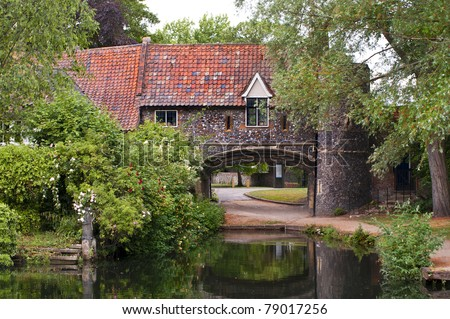 the 15th century arch of Pulls Ferry in the english city of norwich alongside the river yare - stock photo
