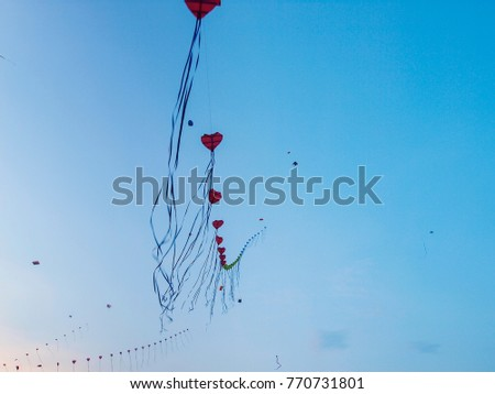 The Thai custom of flying kites at the beginning of winter is expressed here in heart-shaped kites over Sanaam Luang park in Bangkok, Thailand