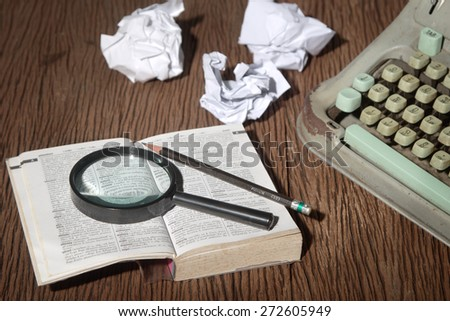 The thai-english dictionary consider under a magnifier on writer's desk with crumpled sheets around   - stock photo