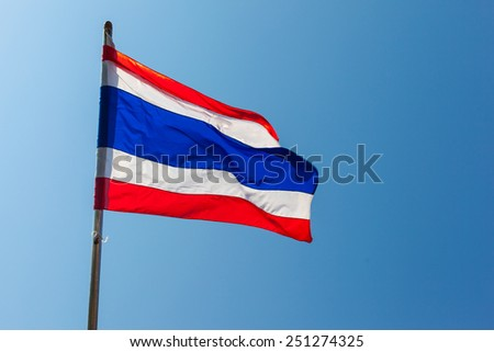 the Thailand flag flapping in the wind over a vibrant blue sky - stock photo