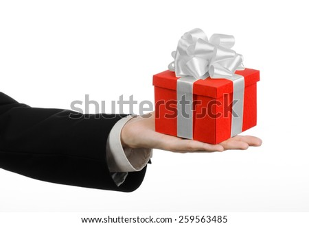 The theme of celebrations and gifts: a man in a black suit holding a exclusive gift wrapped in red box with white ribbon and bow, the most beautiful gift isolated on white background in studio - stock photo