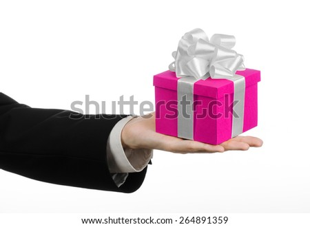 The theme of celebrations and gifts: hand holding a gift wrapped in pink box with white ribbon and bow, the most beautiful gift isolated on white background in studio - stock photo