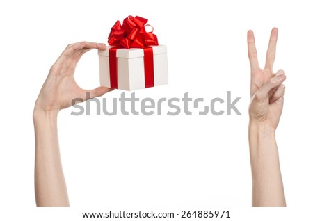 The theme of celebrations and gifts: hand holding a gift wrapped in white box with red ribbon and bow, the most beautiful gift isolated on white background in studio