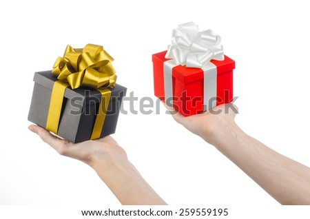 The theme of celebrations and gifts: hand holding two gift wrapped in red box with white ribbon and bow and a black box with gold ribbon, the most beautiful gift isolated on white background in studio - stock photo