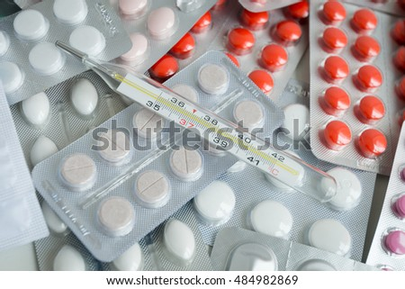 the thermometer with high temperature on packings of tablets, drugs