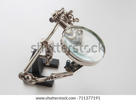 "The ""third hand"" device with clamps and magnifier for holding small parts during soldering with electronic part"