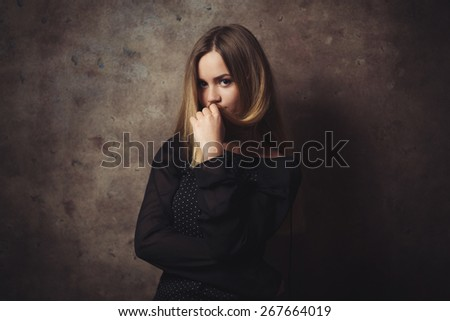 The thoughtful beautiful woman is confused. - stock photo