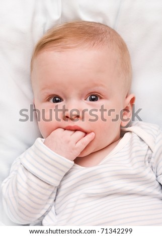 The thoughtful child, hand in a mouth - stock photo