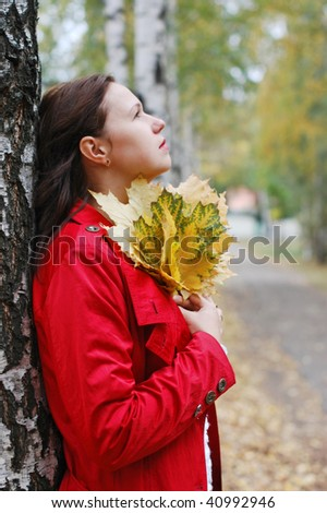 The thoughtful girl with autumn leaves - stock photo