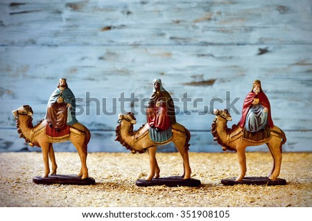 the three kings in their camels carrying their gifts for the Baby Jesus on a rustic nativity scene - stock photo