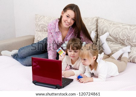 The three sisters make purchases via the Internet on credit cards - stock photo