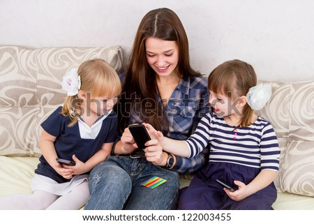 The three sisters with smart-phones - stock photo