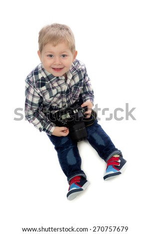 The three-year boy with a camera in hand sitting in the studio on a white background. - stock photo