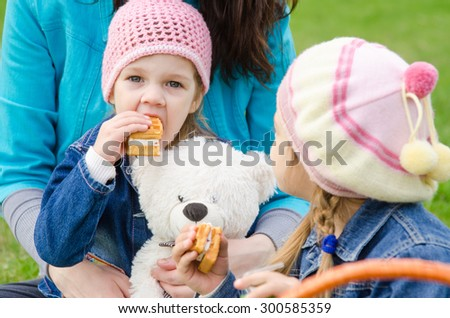 The three-year child eats cake on a picnic on the green lawn