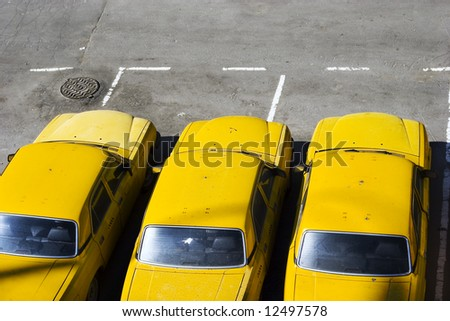 The three yellow taxi cars on parking