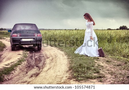 the thrown bride on the rural road with an old suitcase - stock photo
