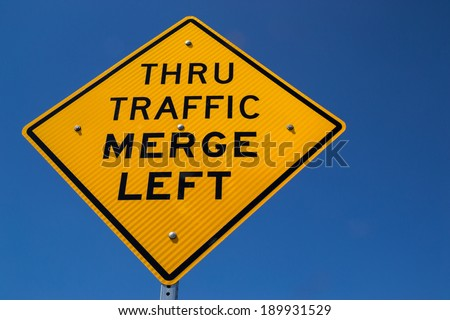 "The ""Thru Traffic Merge Left"" street sign in the Californian sun."