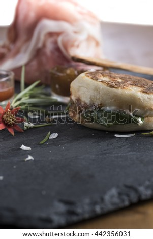 the tigella is a dish very very typical of Emilia, Italy region. It is stuffed with sauces and vegetables and pork cuts - stock photo