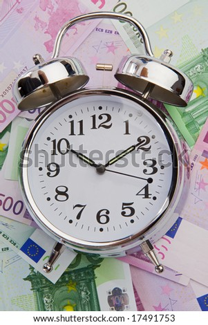 The time is money. Clock with money background - stock photo