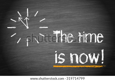 The Time is now - clock with text on blackboard background - stock photo