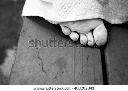 The toes of a child's foot poke out from under a towel.