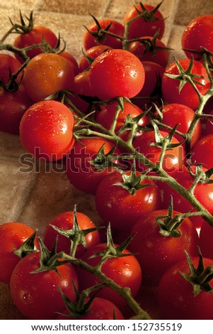 The tomato (Solanum lycopersicum)  is a herbaceous plant in the Solanaceae or nightshade family that is typically cultivated for human consumption. Savory in flavor (so termed a vegetable) - stock photo